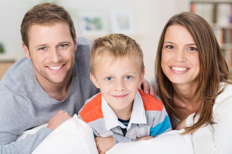 有他微笑的年轻父母的愉快的小男孩 库存图片