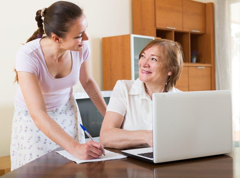 有财政文件的妇女和膝上型计算机在桌上 图库摄影
