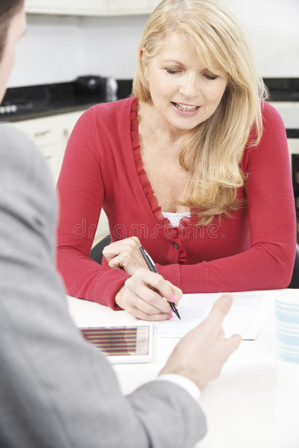 有财政顾问签署的文件的成熟妇女在家 库存图片