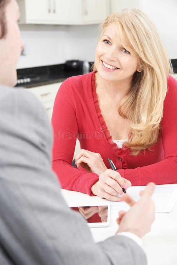 有财政顾问签署的文件的成熟妇女在家 免版税库存照片
