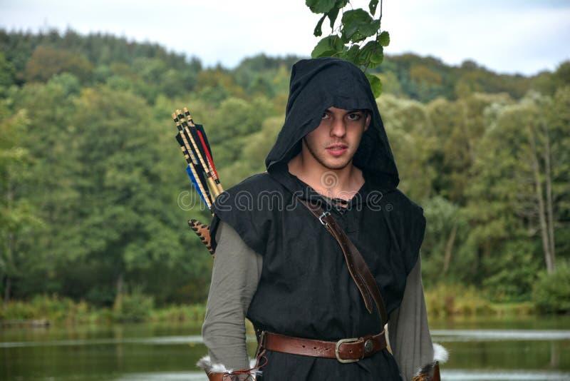 有黑敞篷和箭头的中世纪射手在颤抖在湖前站立并且今后看 免版税库存图片