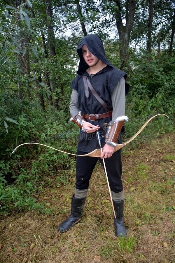 有黑敞篷和色的箭头的中世纪射手在颤抖站立与箭头 免版税图库摄影