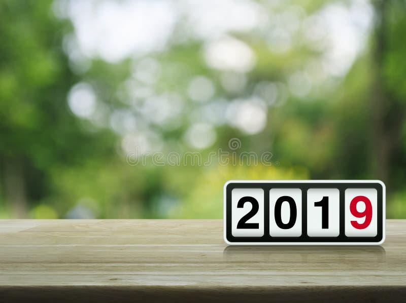有2019文本的减速火箭的轻碰时钟在迷离绿色树的桌上在公园,新年快乐2019盖子概念 库存照片