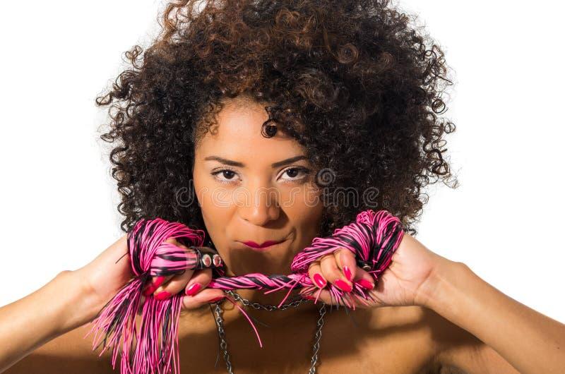 有黑暗卷发藏品鞭子摆在的异乎寻常的美丽的女孩 库存图片