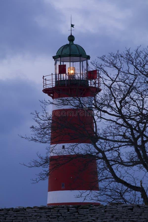 有黑暗的云彩的灯塔在背景中 库存照片