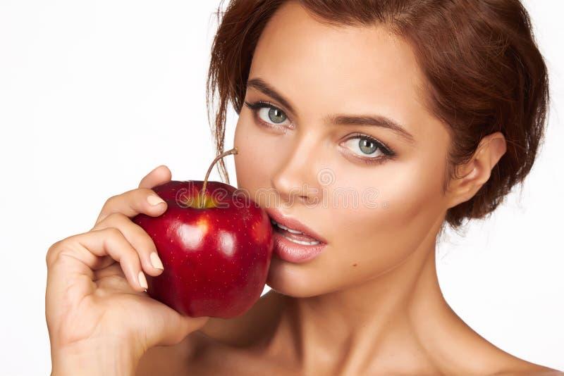 有黑暗的卷发、光秃的肩膀和脖子的年轻美丽的性感的女孩,拿着大红色苹果享受口味和节食, 免版税库存照片