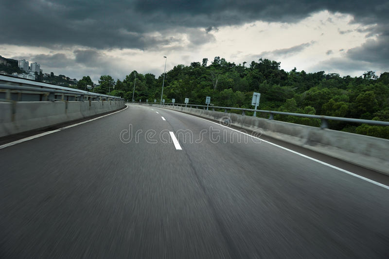 有黑暗的雷雨云和行动迷离的空的城市柏油路 图库摄影