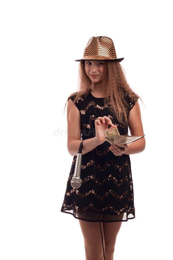 有戴有一个话筒的长的头发的女孩一个黑礼服和金帽子在他的手和金钱在白色背景在螺柱 库存照片