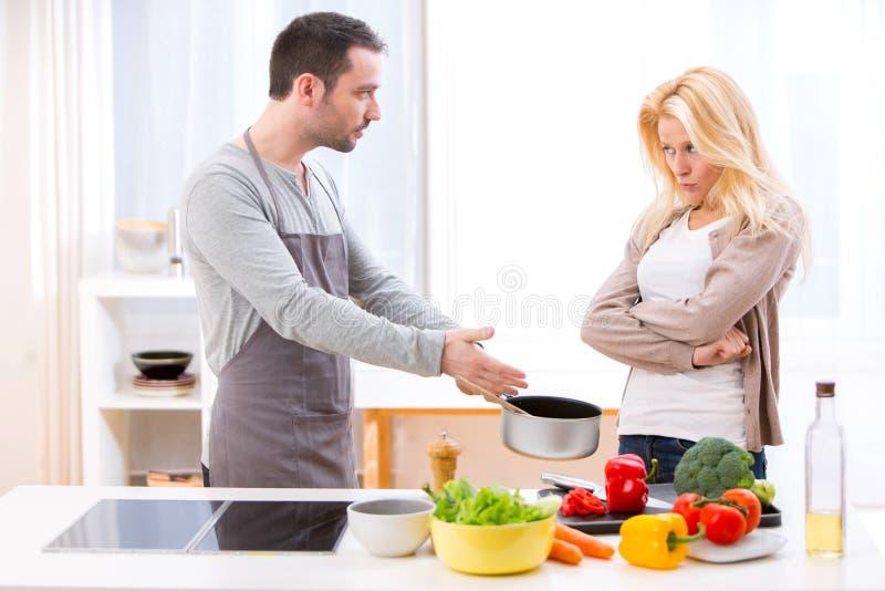 有年轻有吸引力的夫妇争论,当烹调时 免版税库存图片