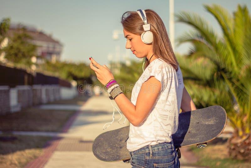 有滑板和耳机听的音乐的女孩户外 库存照片
