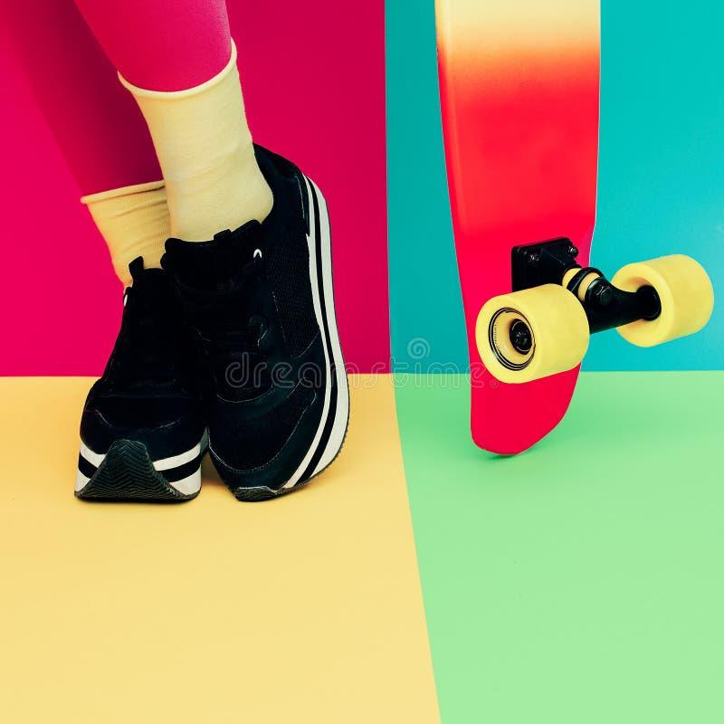 有滑板的时装模特儿腿在明亮的专属backgroun 库存照片