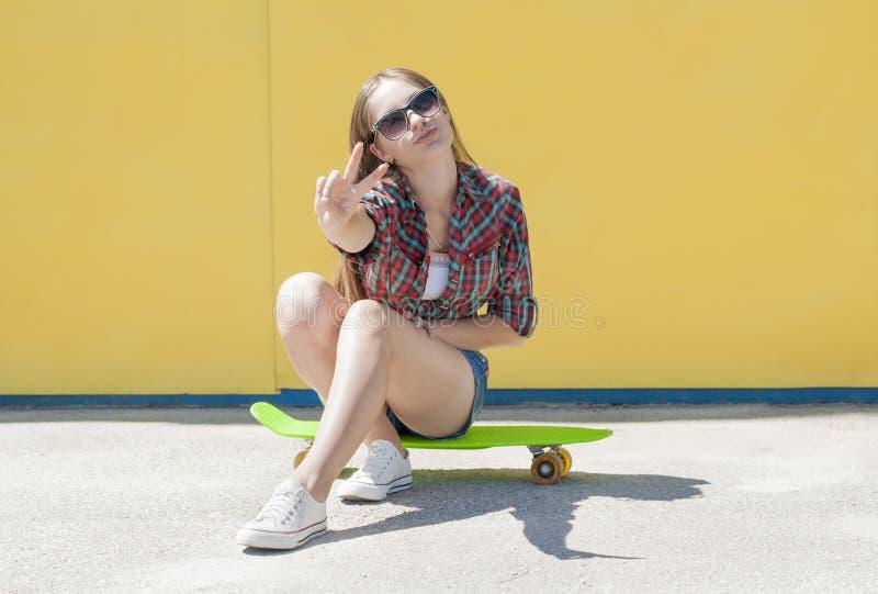 有滑板的时髦的快乐的女孩 免版税库存图片