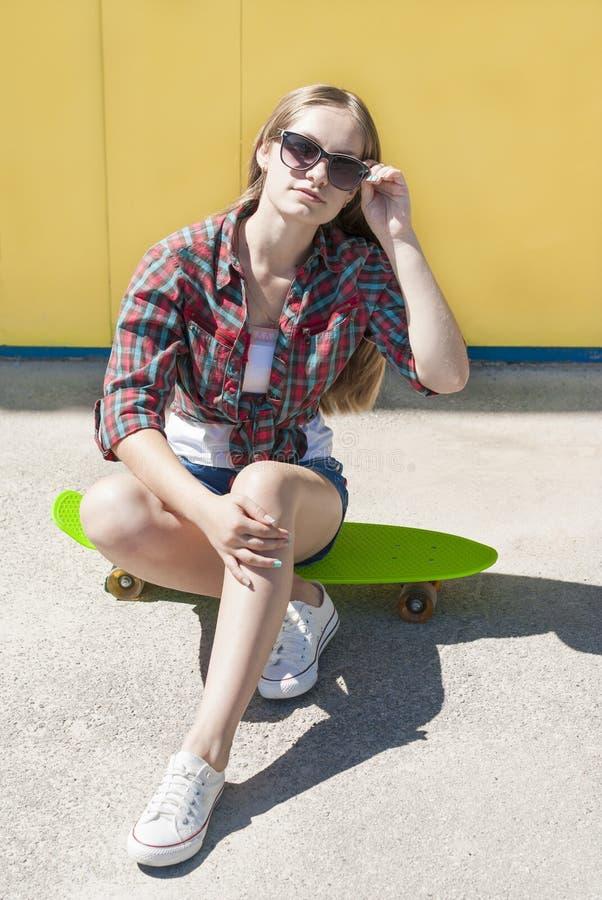 有滑板的时髦的快乐的女孩 图库摄影