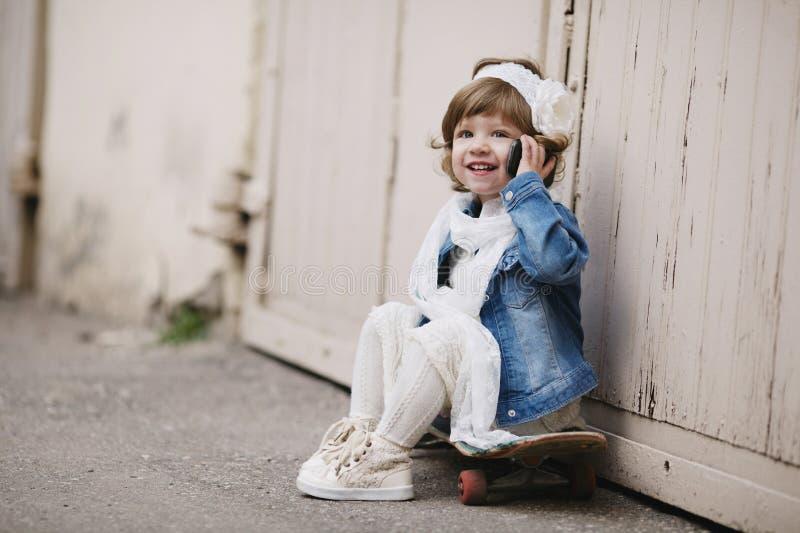 有滑板的逗人喜爱的矮小的行家女孩 图库摄影