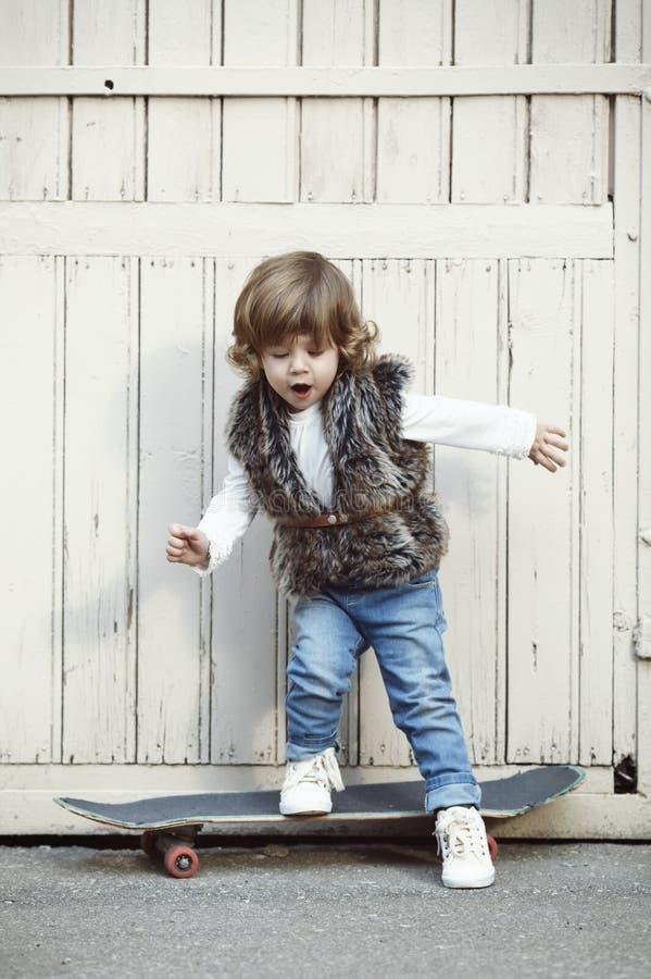 有滑板的逗人喜爱的矮小的行家女孩 库存图片