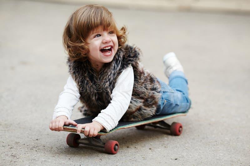 有滑板画象的小行家女孩 免版税图库摄影
