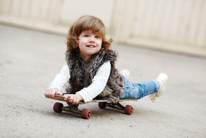 有滑板画象的小行家女孩 免版税库存照片