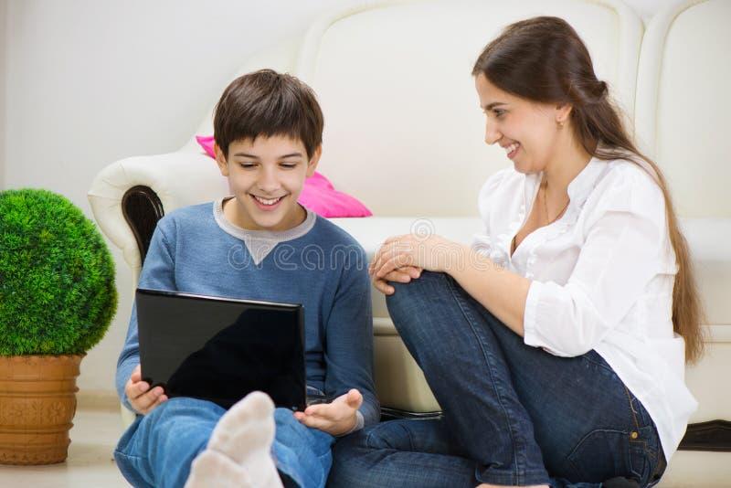 有年轻母亲的青少年的儿子有膝上型计算机的 免版税库存照片