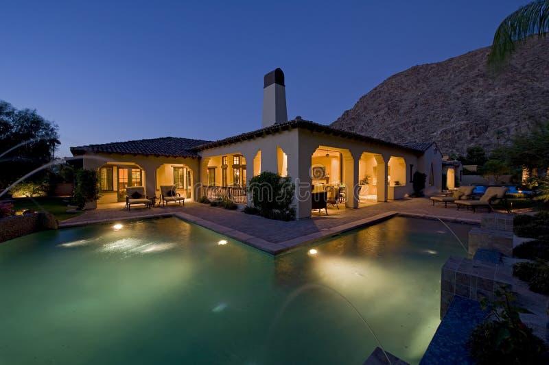 有水池的议院在黄昏的后院 免版税图库摄影