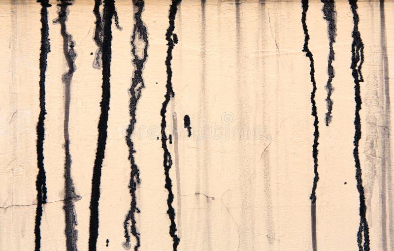 有黑油漆的米黄混凝土墙滴下,抽象背景 免版税图库摄影