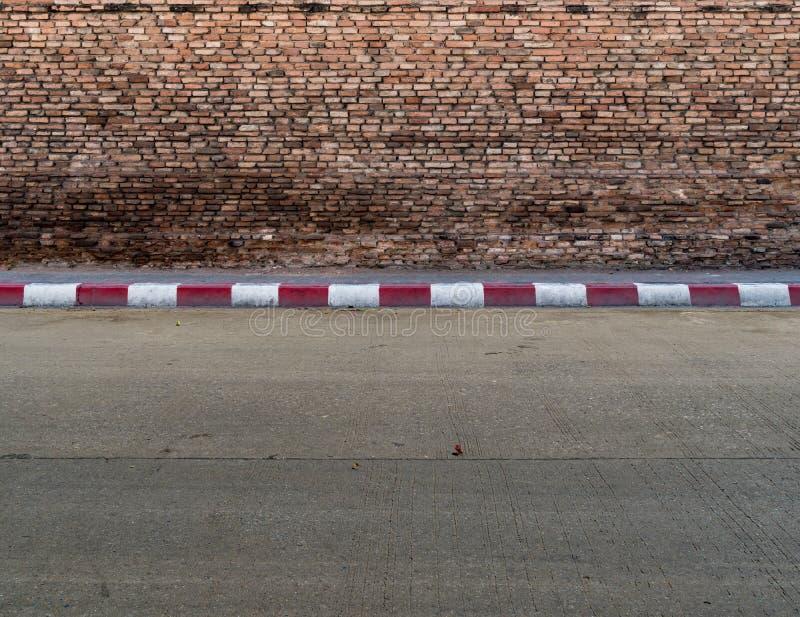 有水泥小路的老砖墙 免版税库存照片