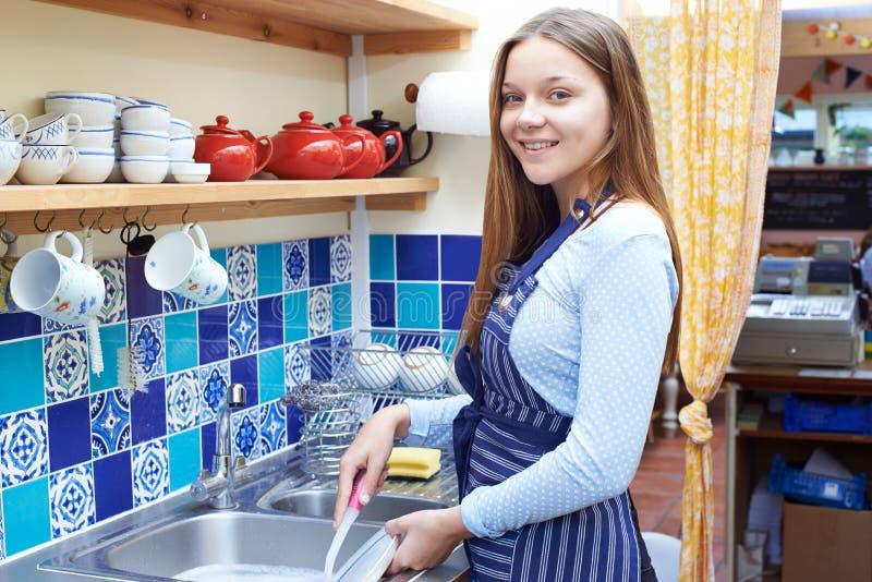 有洗涤在咖啡店的半日工作的十几岁的女孩 图库摄影