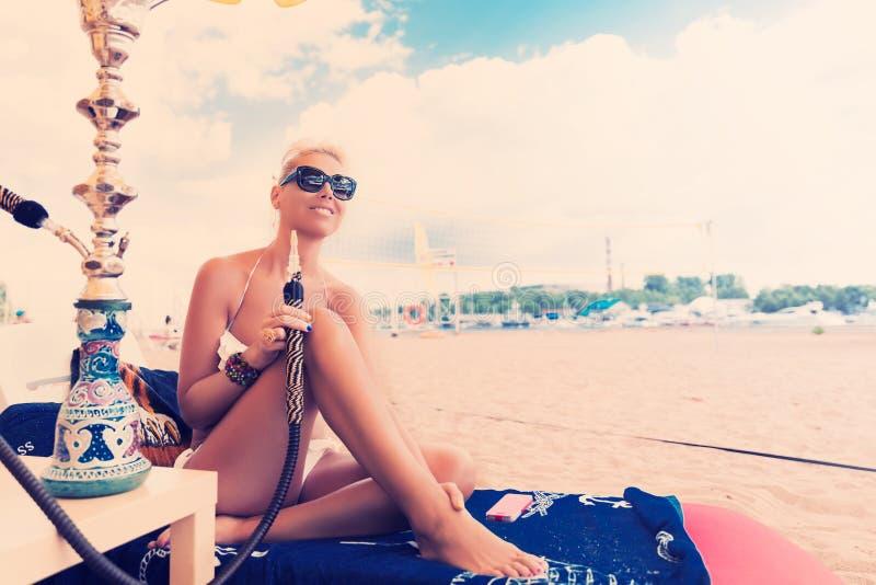 有水烟筒的妇女在比基尼泳装的海滩 库存图片