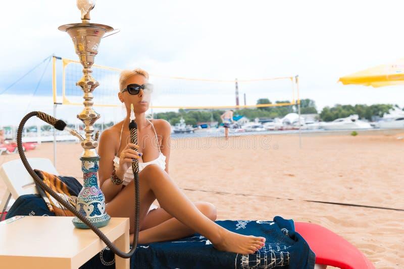 有水烟筒的妇女在海滩 免版税图库摄影