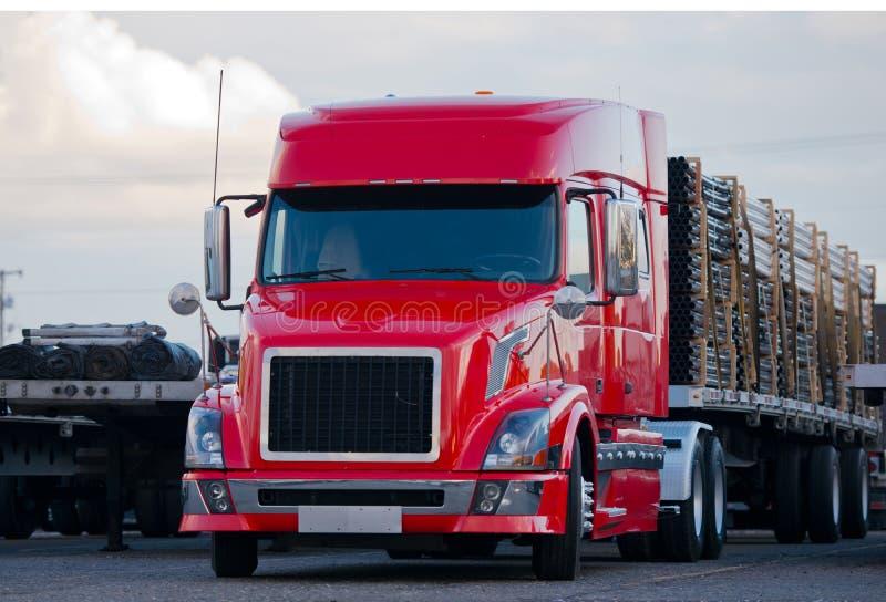有货物的现代半卡车平床拖车在停车场 库存图片