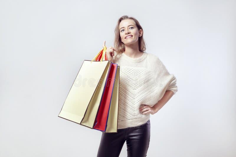 有购物纸袋的白肤金发的美丽的白种人妇女在肩膀 佩带的温暖的毛线衣,微笑 免版税图库摄影