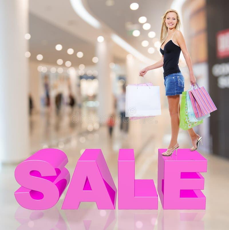 有购物袋姿势的妇女在商店 库存图片