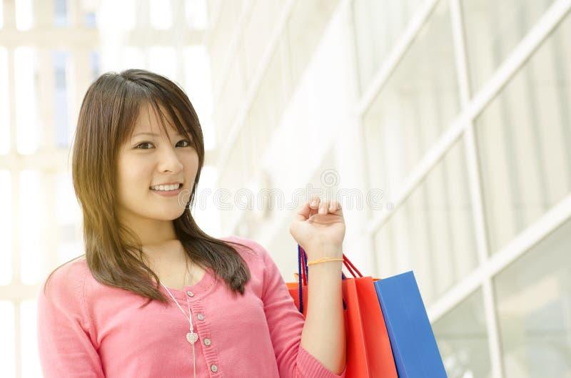 有购物袋的亚裔女孩 免版税库存图片