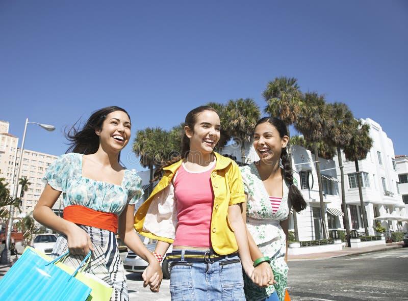有购物袋的十几岁的女孩走在街道上的 图库摄影