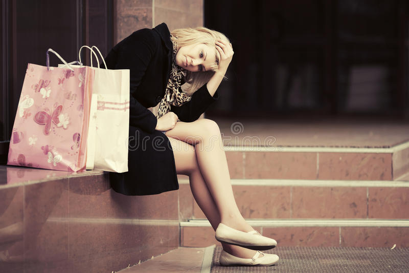 有购物袋的哀伤的少妇在购物中心窗口 库存照片