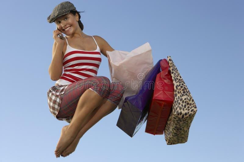有购物袋的妇女使用在空中的手机 免版税库存图片