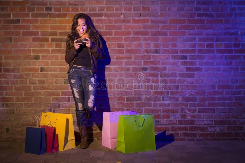 有购物袋的妇女使用手机对砖墙 免版税库存图片