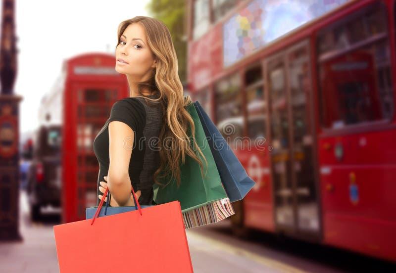 有购物袋的妇女在伦敦市街道 图库摄影