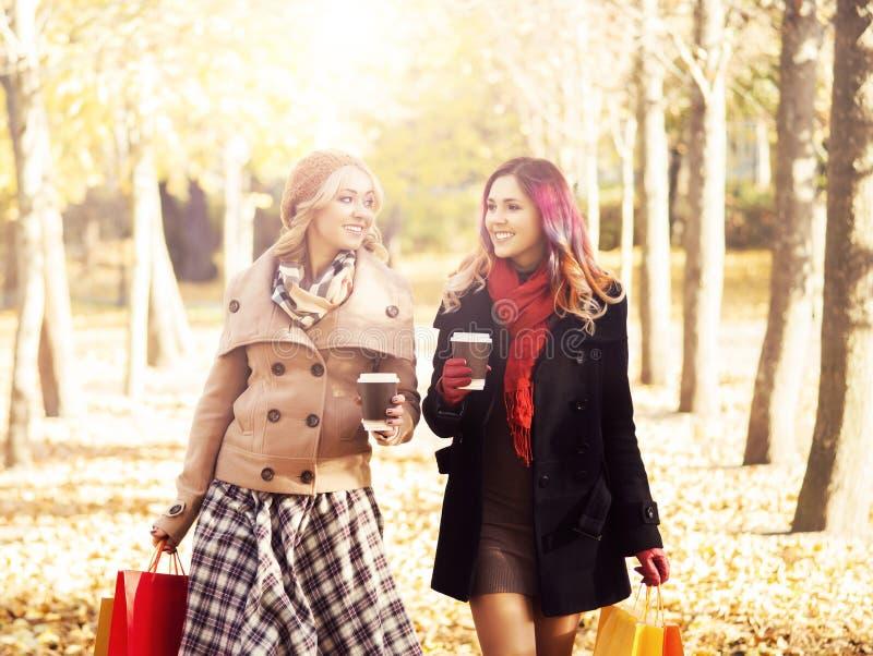 有购物袋的少妇在公园 免版税库存图片