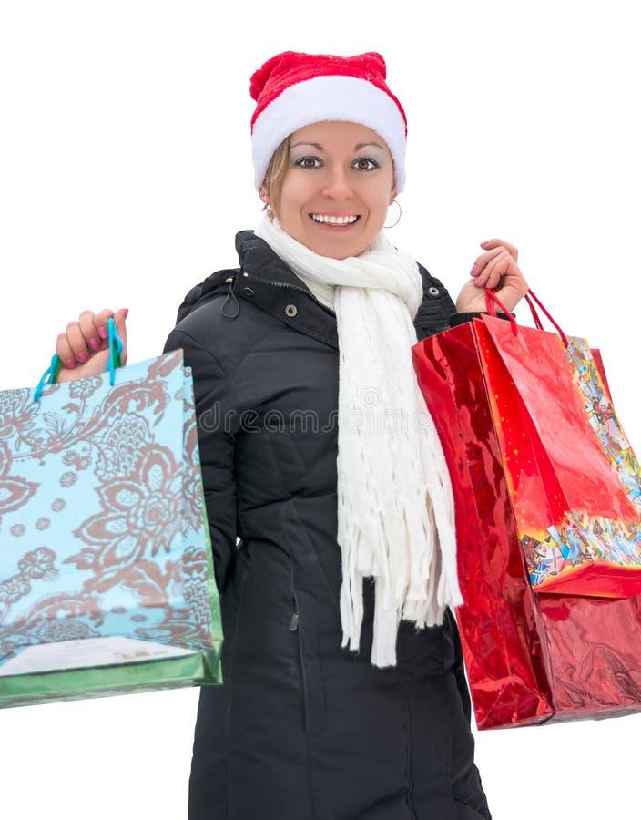 有购物袋的愉快的妇女在圣诞节前,被隔绝 免版税图库摄影