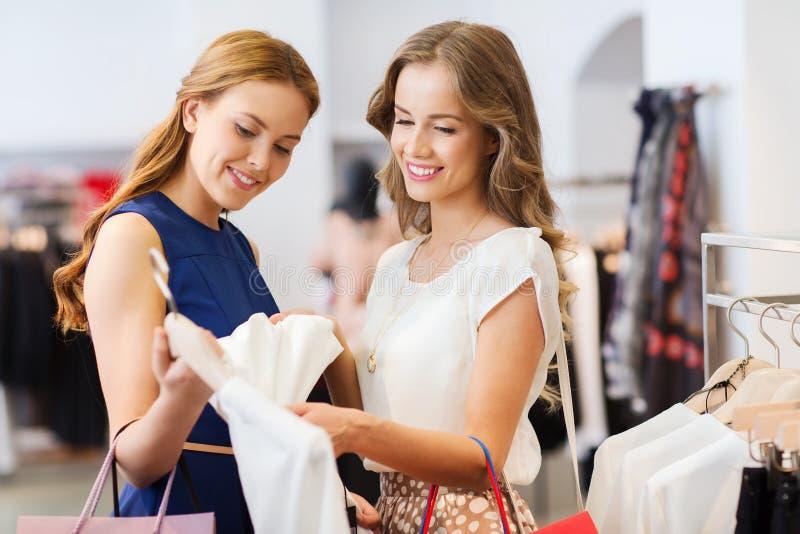 有购物袋的愉快的妇女在衣物购物 免版税图库摄影