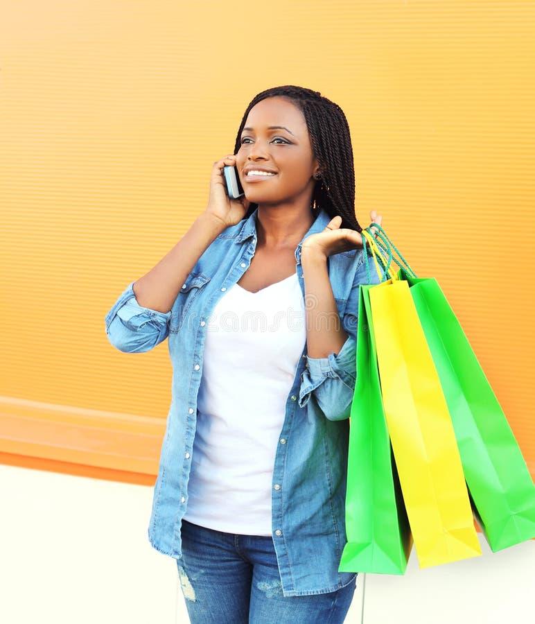 有购物袋的愉快的美丽的微笑的非洲妇女谈话在智能手机 库存照片