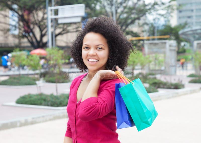 有购物袋的愉快的非裔美国人的妇女在城市 库存照片