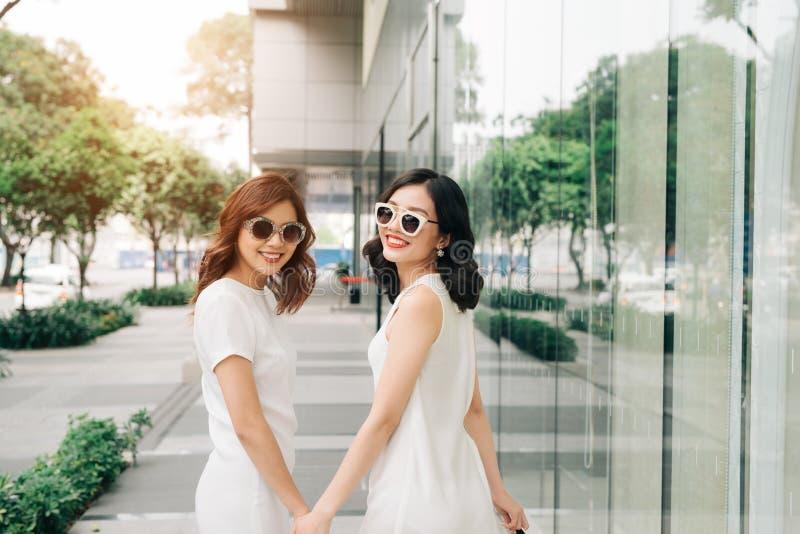 有购物袋的美丽的亚裔女孩走在街道上的在Th 库存图片