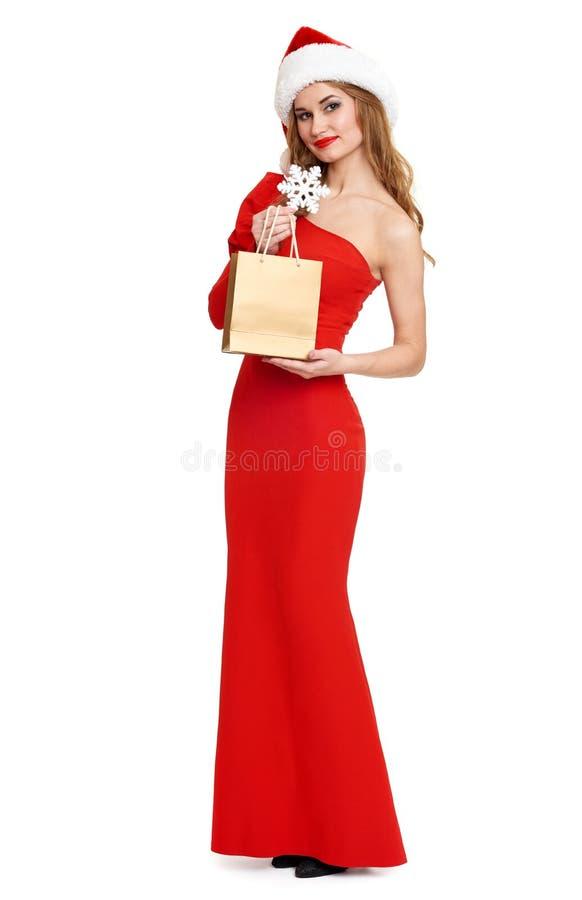 有购物袋的美丽的女孩在红色褂子和在白色背景隔绝的圣诞老人帽子,圣诞节假日概念 免版税库存照片