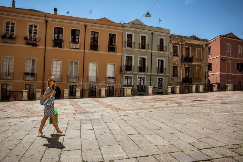 有购物袋的美丽的女孩走通过卡利亚里街道的在撒丁岛 库存照片