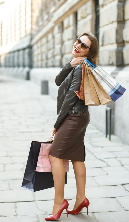 有购物袋的美丽的妇女在ctiy 免版税库存照片