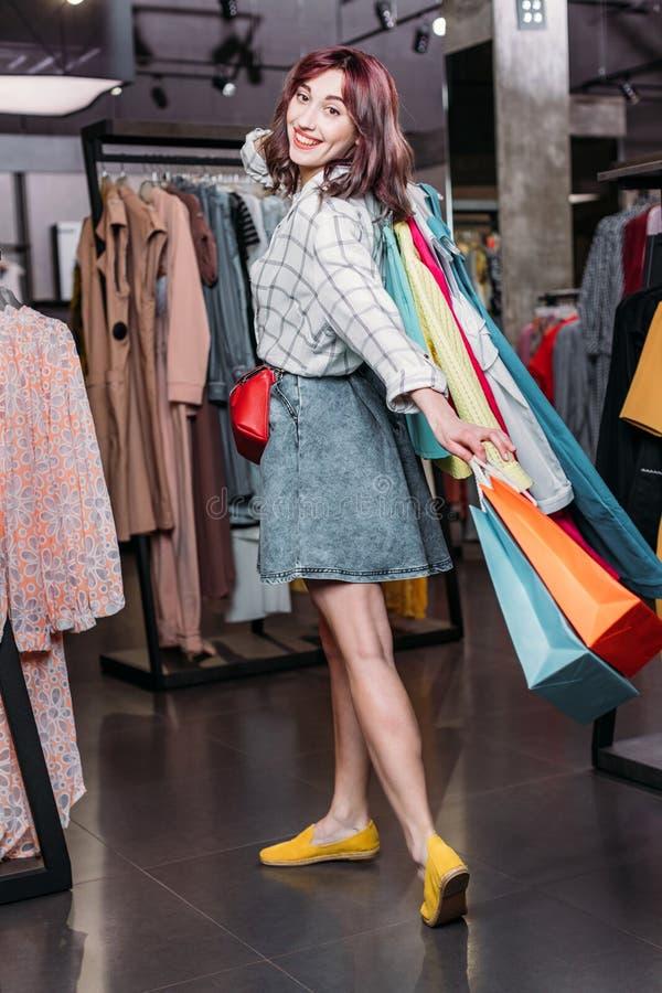 有购物袋的年轻行家女孩在精品店 免版税库存图片