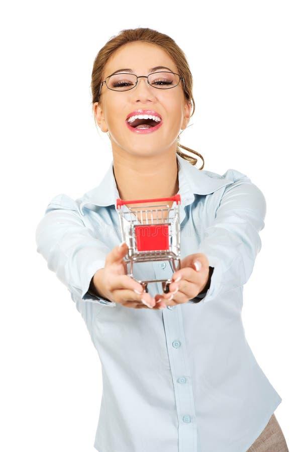 有购物车的可爱的女实业家 免版税库存图片