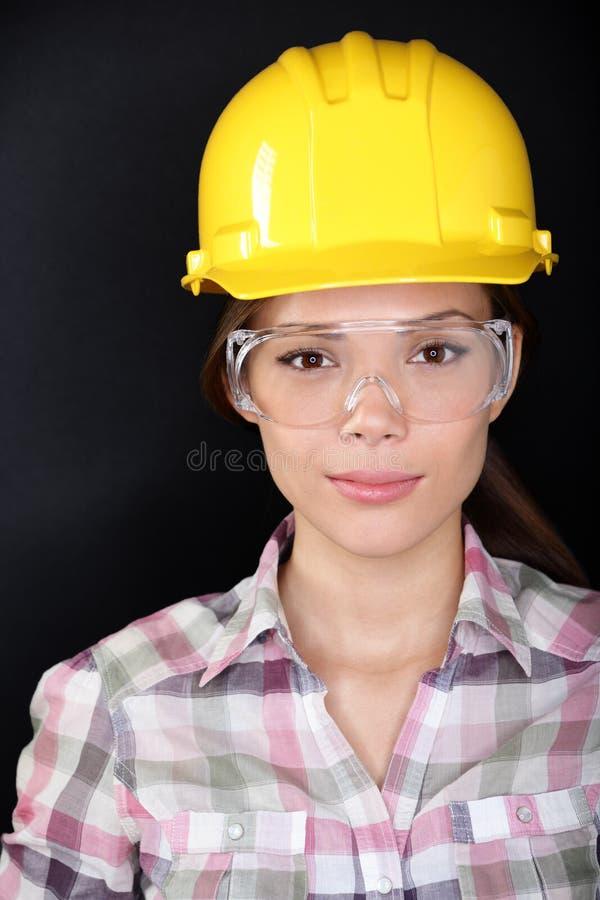 有玻璃和安全帽的建筑工人妇女 库存照片