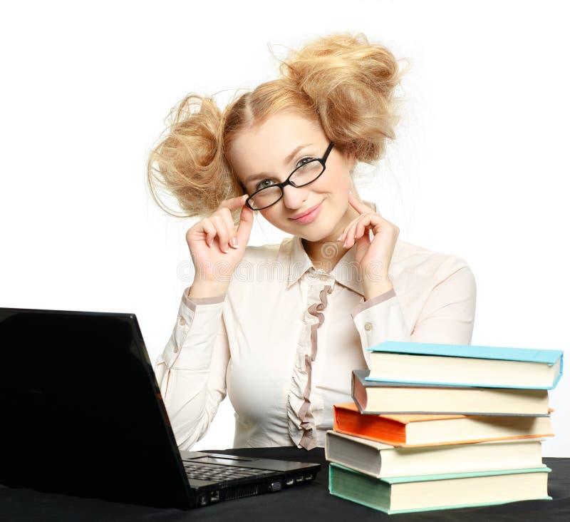 有玻璃工作的美丽的女孩在计算机上 免版税库存图片